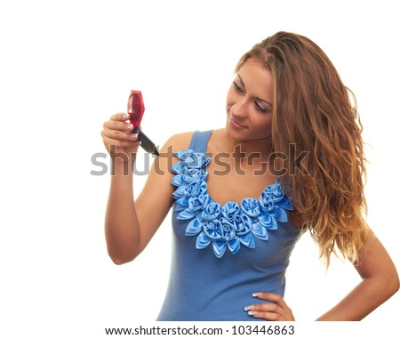 young beautiful girl isolated on a white background looks in the mirror