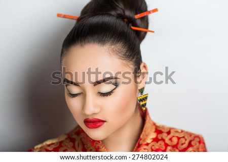 Young beautiful girl, lady, woman, model, Asian. Bright makeup, expressive eyes, arrows, bright red lips. Japan, China, tradition, customs, culture. Image can be used for advertising eastern cuisine - stock photo