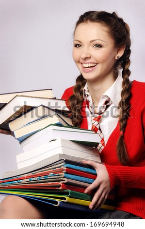 Young beautiful girl laughing catches books - stock photo