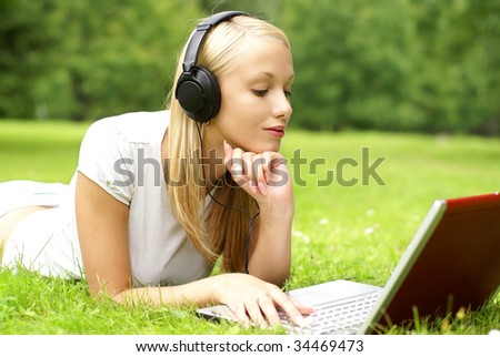 Young beautiful girl listening to the music and using the computer outdoor