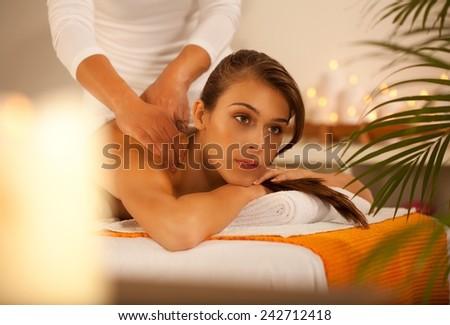 Young beautiful girl lying on massage table and enjoying massage. - stock photo