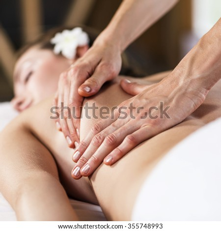 Young beautiful girl lying on massage table and enjoying massage.