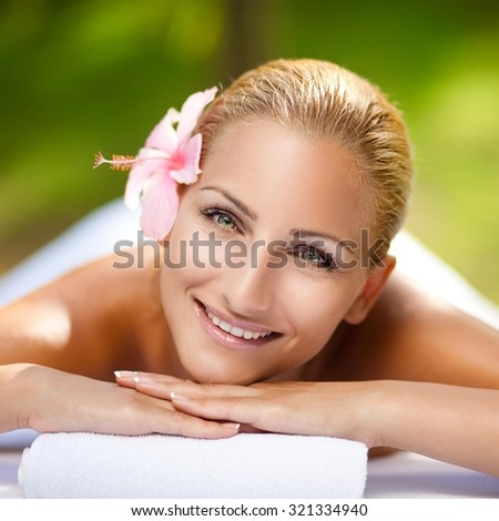 Young beautiful girl lying on massage table in a tropical surroundings. - stock photo