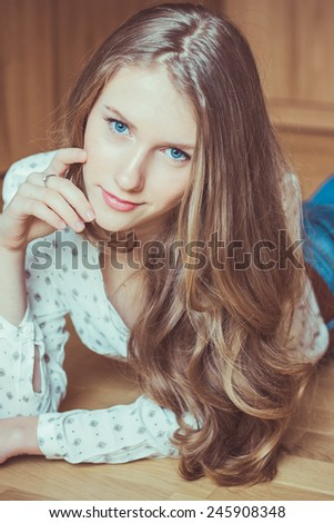 Young beautiful girl lying on wooden floor and looking at camera, studio portrait  - stock photo