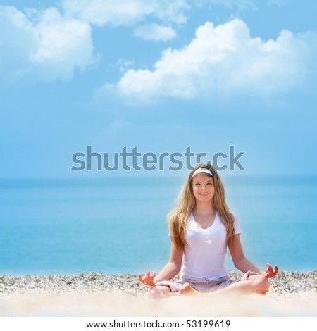 young beautiful girl meditating on beach - stock photo