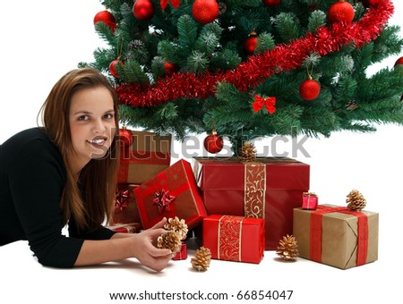 Young beautiful girl near the Christmas tree with lots of presents - stock photo