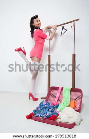 young beautiful girl near the suitcase with clothes and towel. pin up - stock photo
