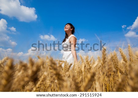 Young beautiful girl on a golden field of wheat looking upwards and enjoy life - stock photo