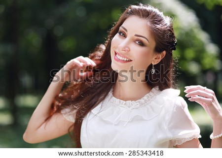 young beautiful girl on a meadow enjoying sun and fresh air - stock photo
