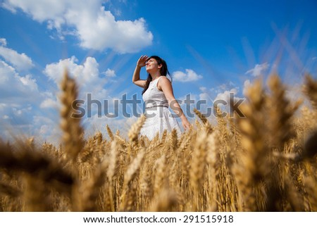 Young beautiful girl on field of wheat looking upwards and enjoy life - stock photo