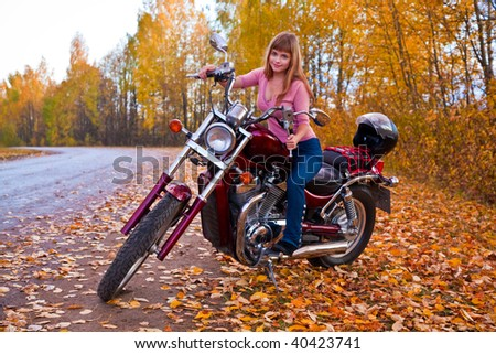 Young beautiful girl on motorcycle. Autumn - stock photo