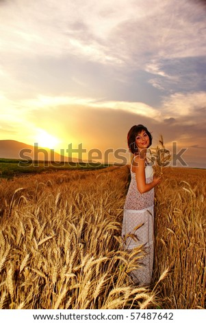 Young beautiful girl on the cornfield