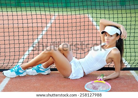 Young, beautiful girl on the tennis court  - stock photo
