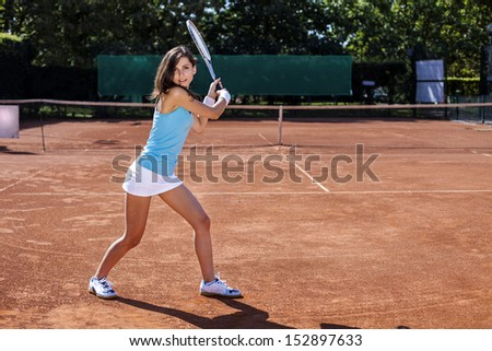Young, beautiful girl on the tennis court on a beautiful sunny day