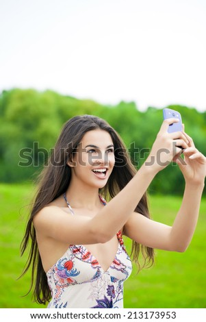 Young beautiful girl photographed on a cell phone in a summer park