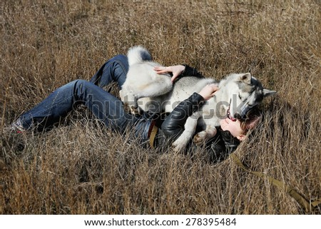 Young beautiful girl playing with a dog. Playing with the dog on the field. Siberian husky.