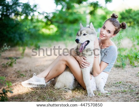 Young beautiful girl playing with a dog. Playing with the dog on the park. Close-up portrait. Siberian husky. - stock photo