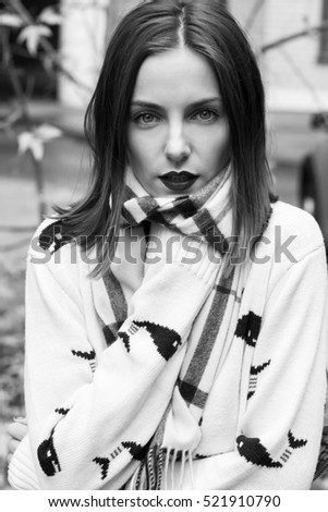 young beautiful girl portrait with natural make up and red lips and short brown hairs in white pullover in street bw
