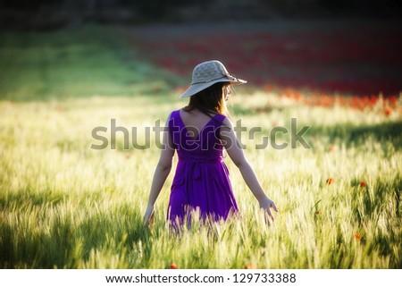 Young beautiful girl posing in a green field. - stock photo