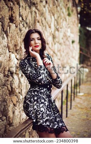 Young beautiful girl posing near a stone wall - stock photo