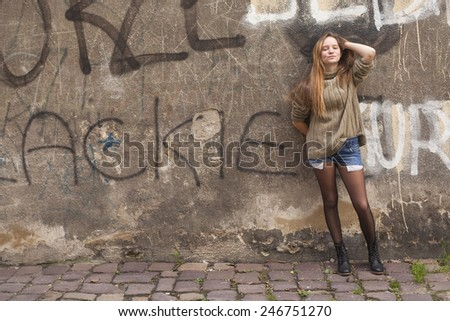 Young beautiful girl posing near a stone wall in the old town. - stock photo