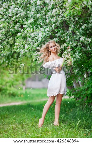 Young beautiful girl posing near apple-tree in blossom - stock photo