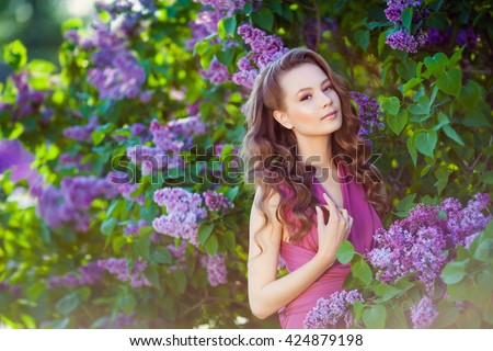 Young beautiful  girl posing near lilac bushes in blossom
