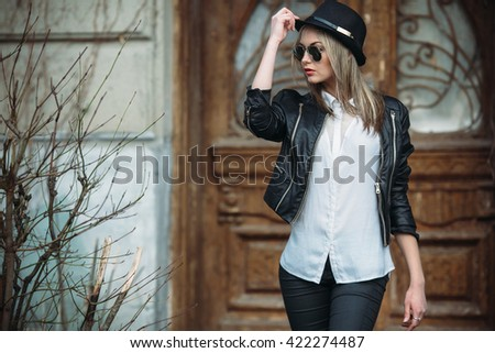 Young beautiful girl posing on a background of an old building