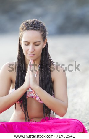 Young beautiful girl practicing yoga on the beach - stock photo