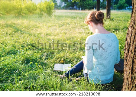 young beautiful girl reading a book in the park - stock photo