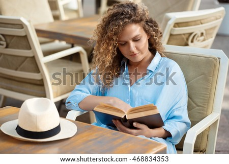 Young beautiful girl reading, sitting in cafe.