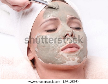 Young beautiful girl receiving clay facial mask in spa beauty salon - stock photo