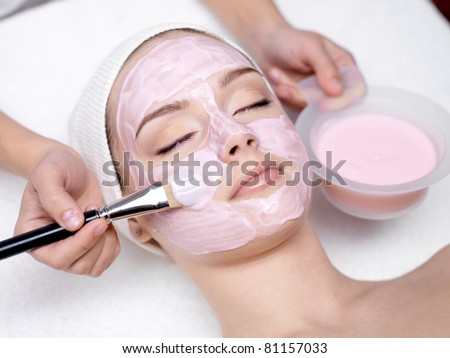 Young beautiful girl receiving pink facial mask in spa beauty salon - indoors - stock photo