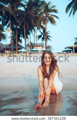 Young beautiful girl relaxing on Thailand beach over palm view - stock photo
