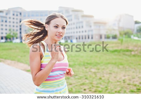 Young beautiful girl running at sunset at her university campus park during evening workout training session. Wearing striped sleeveless shirt - stock photo