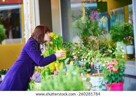 Young beautiful girl selecting flowers in a Parisian outdoor flower shop - stock photo