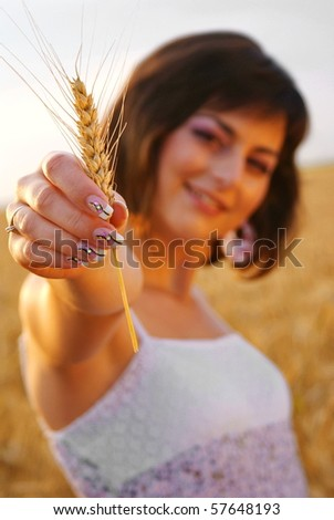 Young beautiful girl showing a corn with her hand