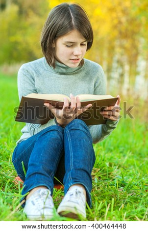 Young beautiful girl sits on bridge and reads interesting book. - stock photo