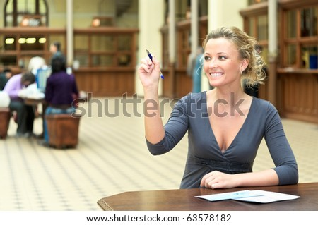 Young beautiful girl sitting at the table and writing with a pen in air. Copy space