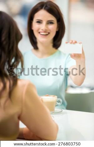 Young beautiful girl sitting in cafe with her friend and showing  new business card. - stock photo