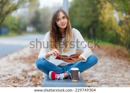 Young beautiful girl sitting on a bench in a park - stock photo
