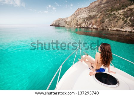 young beautiful girl sitting on a yacht at sea. Relaxing on the water. woman resting on the water - stock photo