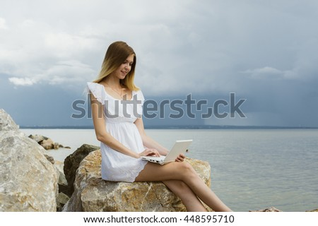 Young beautiful girl sitting on the rocks by the sea, working with a laptop - stock photo