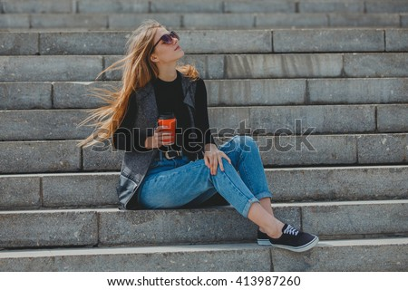 Young beautiful girl sitting on the steps with coffee in glasses.