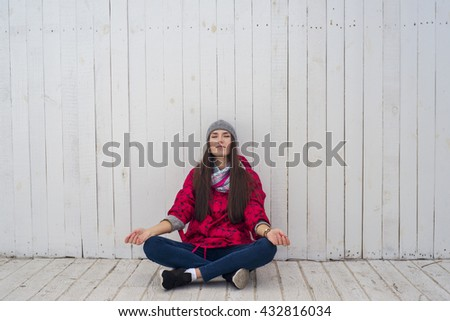 Young beautiful girl sitting on white wooden floor and meditating with eyes closed - stock photo