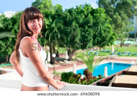 Young beautiful girl standing on the balcony of the hotel and looking at camera. One Caucasian woman smiling close up - stock photo