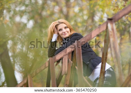 Young beautiful girl standing on the bridge, leaning on the railing and looking pensively into the distance