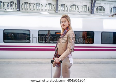 young beautiful girl standing on the platform while waiting for a train. modern businesswoman goes on a business trip by train