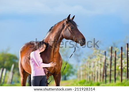 Young beautiful girl standing with a horse in garden - stock photo