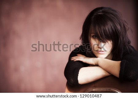 Young beautiful girl staring at camera with messy casual hairstyle.